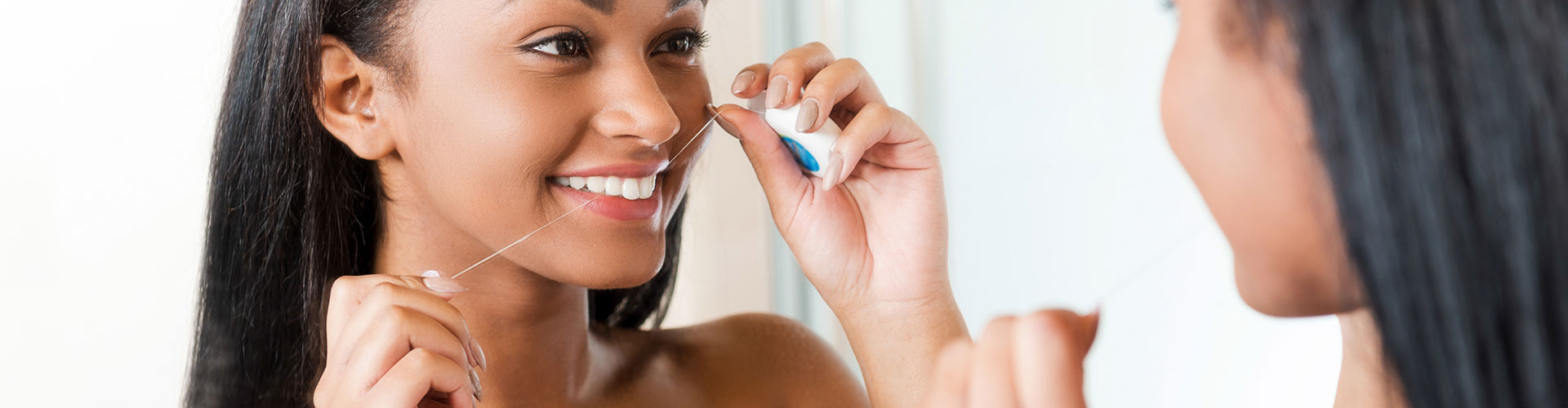 A woman flossing infront of mirror